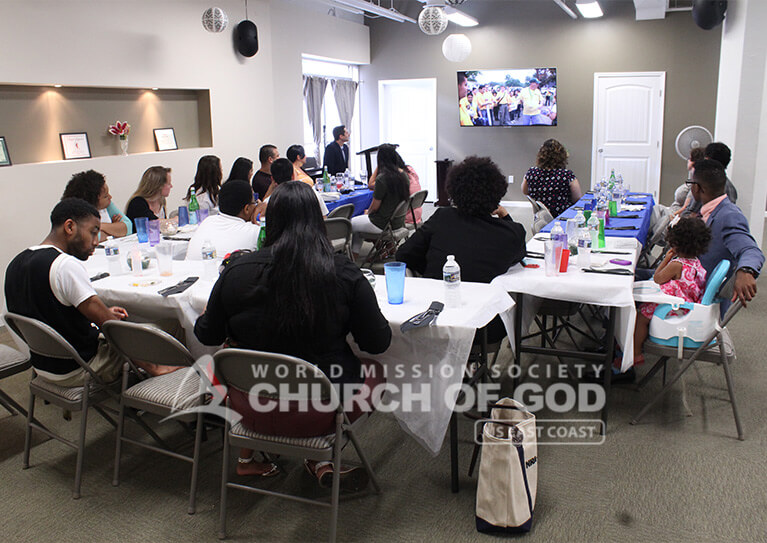 Guests watching World Mission Society Church of God introduction video during a Father's Day Appreciation Dinner in Louisville, KY